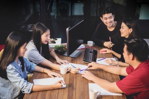 Gruppo indipendente asiatico che spiana per il lavoro di squadra nella sala riunioni dell'ufficio Foto Premium