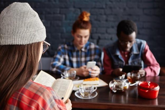 Gruppo multietnico di giovani studenti alla moda che bevono tè al caffè durante la pausa: donna in cappello libro di lettura mentre donna rossa e uomo africano con gadget elettronici. Foto Gratuite