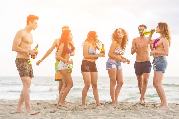 Gruppo multirazziale di amici che hanno una festa in spiaggia Foto Premium