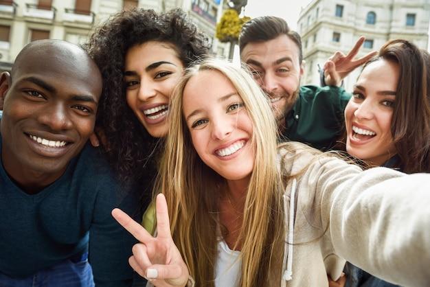 Gruppo multirazziale di giovani che prendono selfie Foto Gratuite