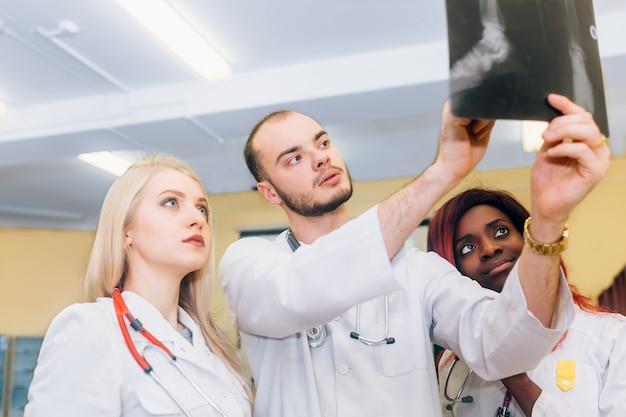 Gruppo multirazziale di giovani medici che esaminano il concetto medico e di radiologia di sanità dei raggi x Foto Premium