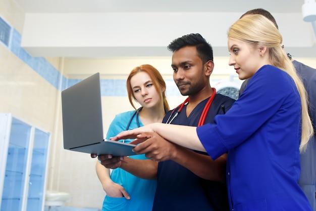 Gruppo multirazziale di giovani medici che lavorano al computer portatile in ufficio medico. Foto Premium