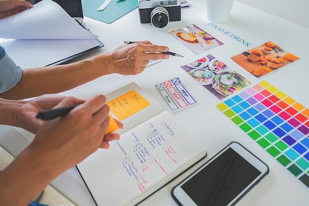 Gruppo start-up creativo del progettista asiatico di pubblicità che discute le idee in ufficio. Foto Premium