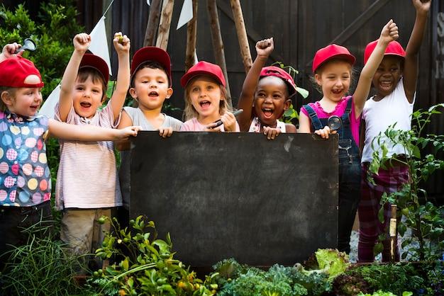 Gruppo vario di bambini allegri che tengono una lavagna Foto Premium
