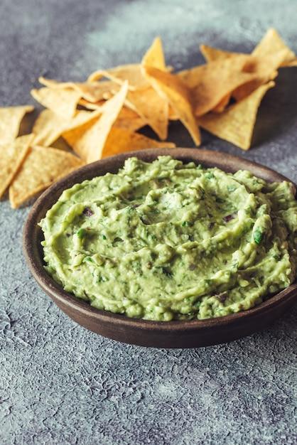 Guacamole in una ciotola con tortilla chips Foto Premium