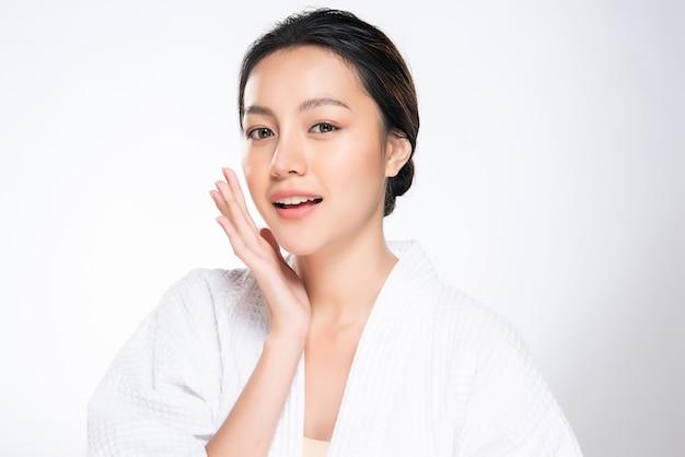 Guancia e tocco molli commoventi della bella giovane donna asiatica con pelle pulita e fresca. felicità e allegria con, isolato su bianco, bellezza e cosmesi, Foto Premium