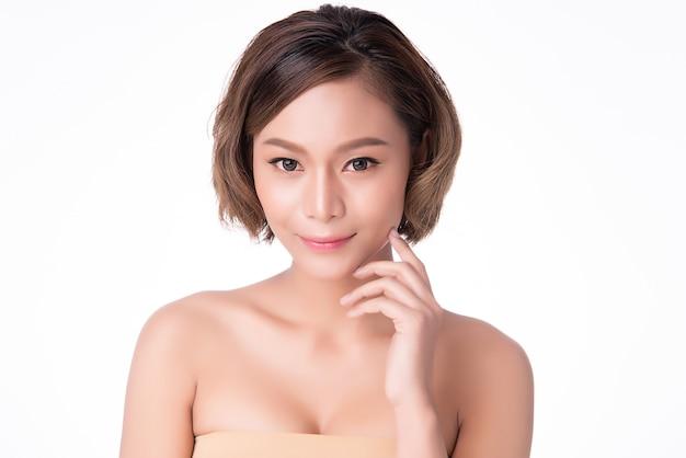 Guancia e tocco molli commoventi della bella giovane donna asiatica con pelle pulita e fresca Foto Premium