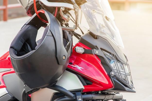 Guanti da moto e casco di sicurezza appesi su un sedile anteriore della moto sportiva per motivi di sicurezza Foto Premium
