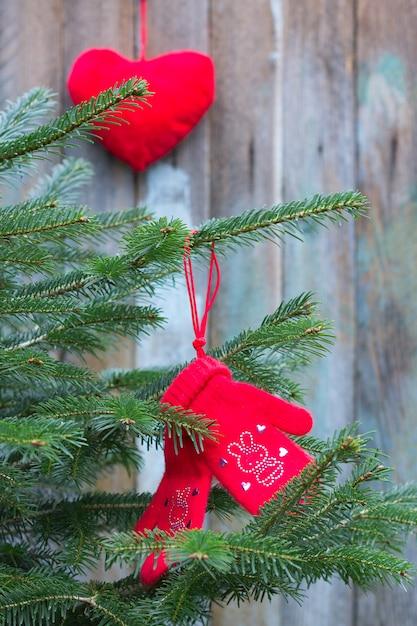Guanti lavorati a maglia in lana di cammello di colore rosso decorati con strass rossi cuori coniglietti sul ramo di un albero di natale su uno sfondo di vecchie tavole e giocattoli di natale a forma di cuore Foto Premium