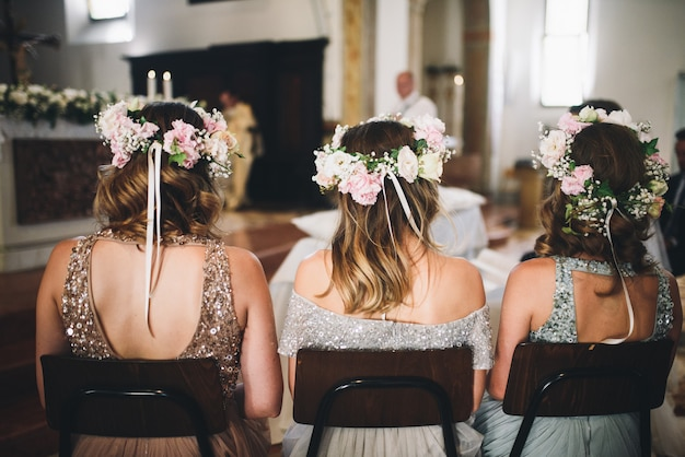 Guarda da dietro alle damigelle che siedono sulle sedie del chu Foto Gratuite