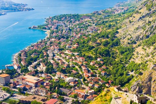 Guardando oltre la baia di kotor in montenegro con vista sulle montagne, barche e vecchie case con tetti di tegole rosse Foto Premium
