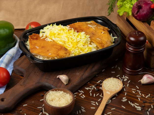 Guarnire il riso, plov da asporto in un contenitore nero su tavola di legno. Foto Gratuite