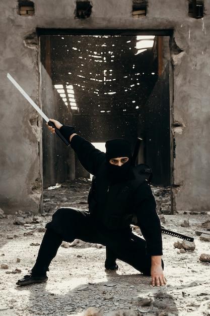 Guerriero ninja in abiti neri con un dispiacere Foto Gratuite