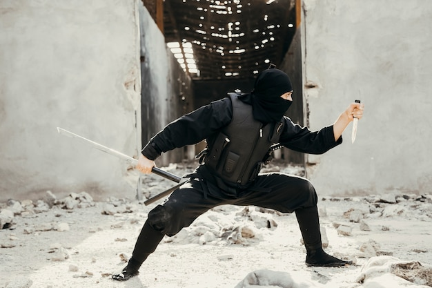 Guerriero ninja mostrando trucchi in abiti neri in possesso di un dispiacere Foto Gratuite