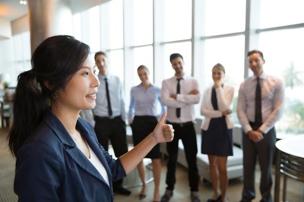Guida femminile di affari con il pollice alto Foto Gratuite