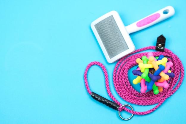 Guinzaglio dell'animale domestico con il giocattolo di gomma su fondo blu Foto Premium