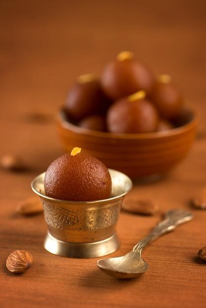 Gulab jamun in ciotola e ciotola antica in rame con cucchiaio. dessert indiano o piatto dolce. Foto Premium