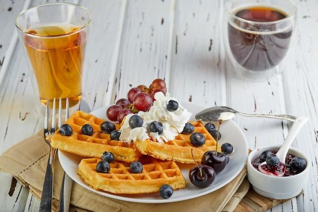 Gustosa colazione cialde belghe con mirtilli panna montati e marmellata su un bianco di legno Foto Premium