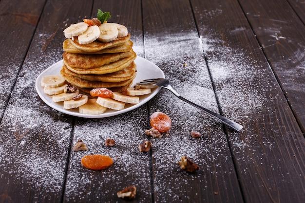 Gustosa colazione i puncakes deliziosi con le banane, i dadi e la menta sono servito sul piatto bianco Foto Gratuite