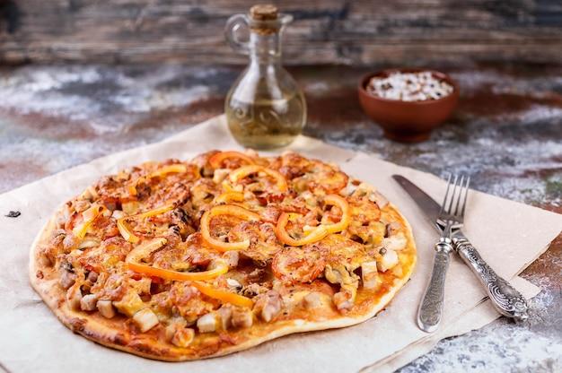 Gustosa pizza con pollo, peperoni e formaggio su legno Foto Premium