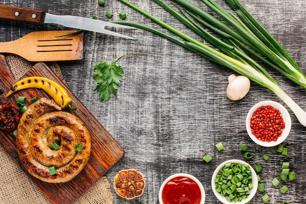 Gustose salsicce alla griglia e verdure fresche sul vecchio fondale Foto Gratuite