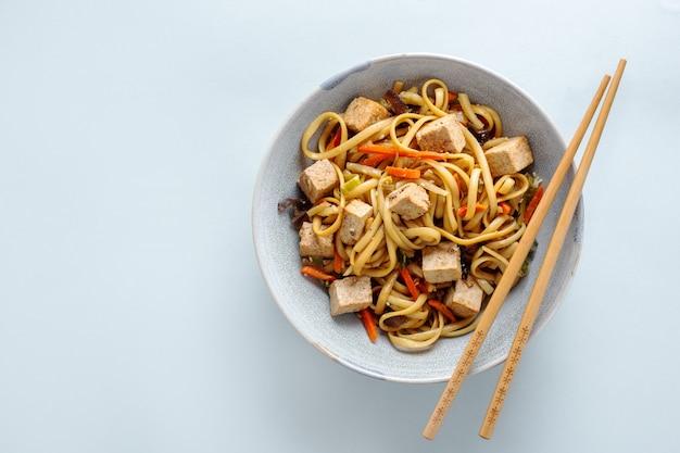 Gustose tagliatelle asiatiche con formaggio tofu e verdure su piatti. orizzontale. Foto Gratuite