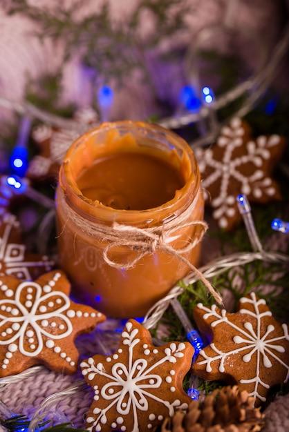 Gustosi e profumati biscotti al cioccolato sono schiacciati con zucchero a velo, con luci multicolori sul tavolo. buon natale Foto Premium