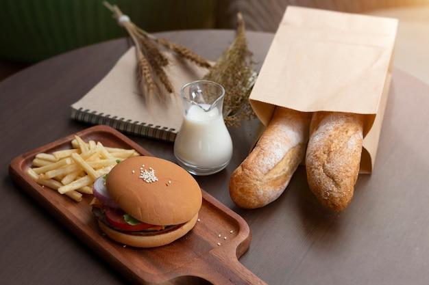 Gustosi hamburger fatti in casa alla griglia, pane e patatine fritte in legno. Foto Premium