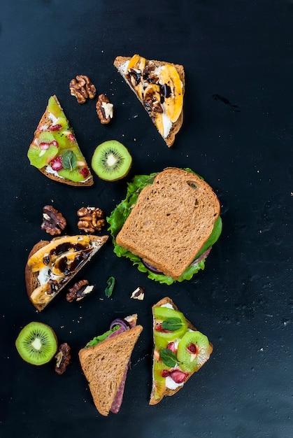 Gustosi panini dolci con banane, noci e cioccolato, kiwi, fragole e menta su sfondo nero Foto Premium