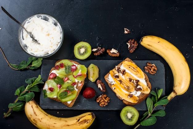 Gustosi panini dolci con banane, noci e cioccolato, kiwi, fragole e menta Foto Premium