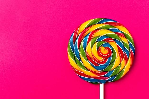 Gustoso appetitoso partito accessorio sweet swirl candy lollypop su sfondo rosa vista superiore Foto Gratuite