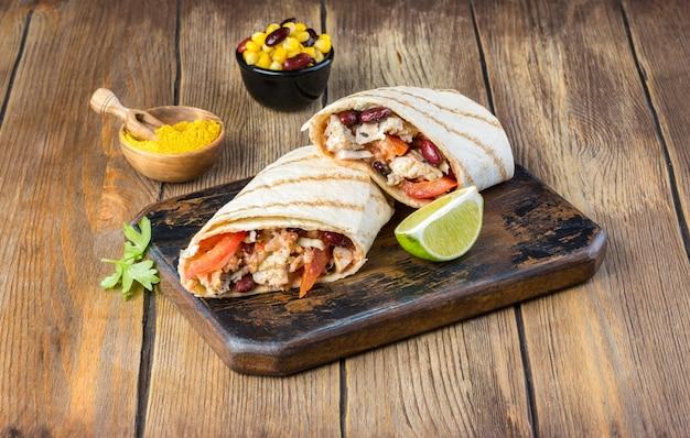 Gustoso burrito messicano con verdure, salsa piccante e lime Foto Premium