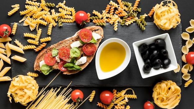Gustoso cibo italiano con pasta cruda; olive nere e scodella d'olio sulla superficie nera Foto Gratuite
