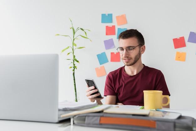 Guy a una scrivania guardando il suo telefono Foto Gratuite