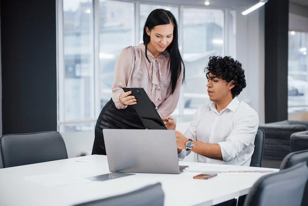 Guy spiega il significato del documento. il ragazzo riccio e la ragazza castana discutono i dettagli del contratto in ufficio moderno Foto Premium
