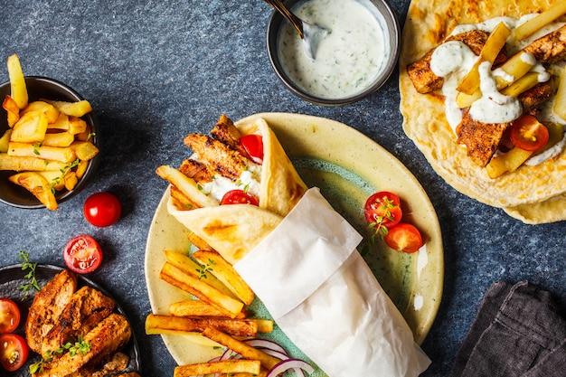Gyros souvlaki si avvolge nel pane pita con pollo, patate e salsa tzatziki, sfondo di ingredienti. Foto Premium