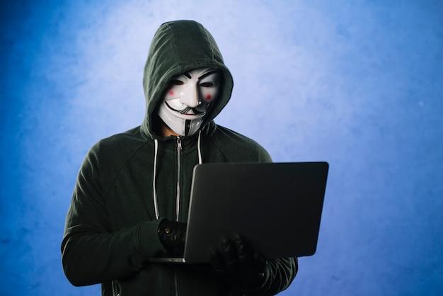 Hacker con maschera anonima Foto Gratuite