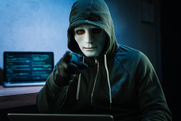Hacker con maschera davanti al computer portatile Foto Gratuite