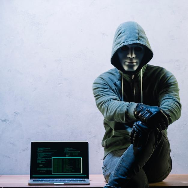 Hacker seduto accanto al computer portatile Foto Gratuite