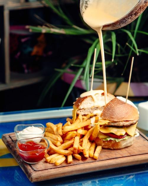Hamburger al formaggio con patatine fritte sul tavolo Foto Gratuite
