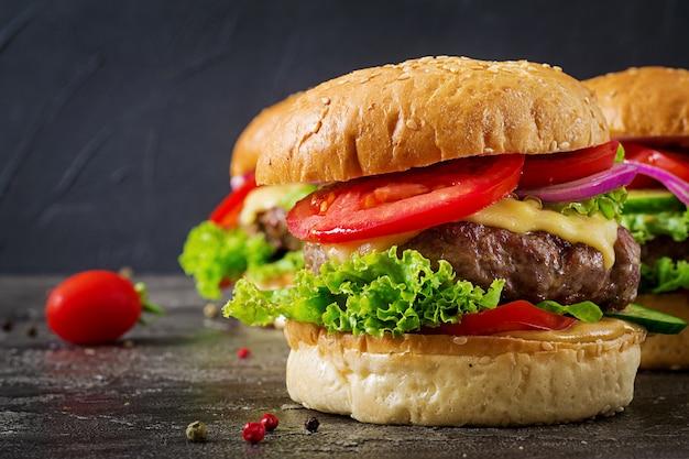 Hamburger con hamburger di carne di manzo e verdure fresche su sfondo scuro. cibo gustoso. Foto Premium