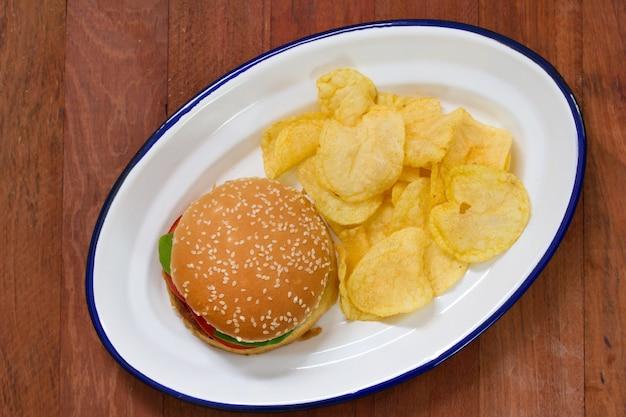 Hamburger con le patatine fritte sul piatto bianco sulla tavola marrone Foto Premium
