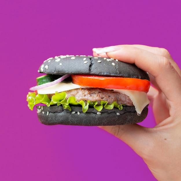 Hamburger con panino nero su sfondo viola Foto Gratuite