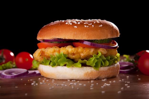 Hamburger con pollo, insalata, cetrioli, pomodori e cipolle su sfondo nero. Foto Premium