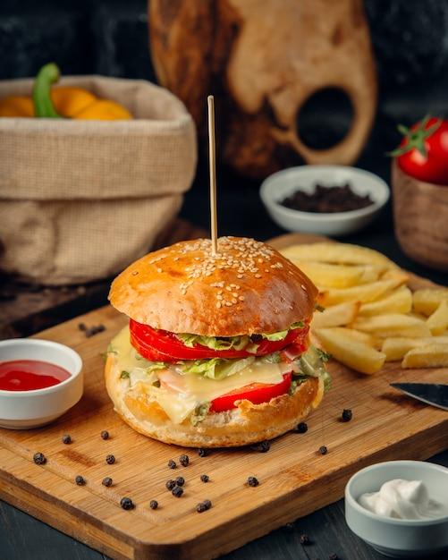 Hamburger con pomodoro, lattuga, formaggio fuso e patatine fritte, ketcup, primi piani Foto Gratuite