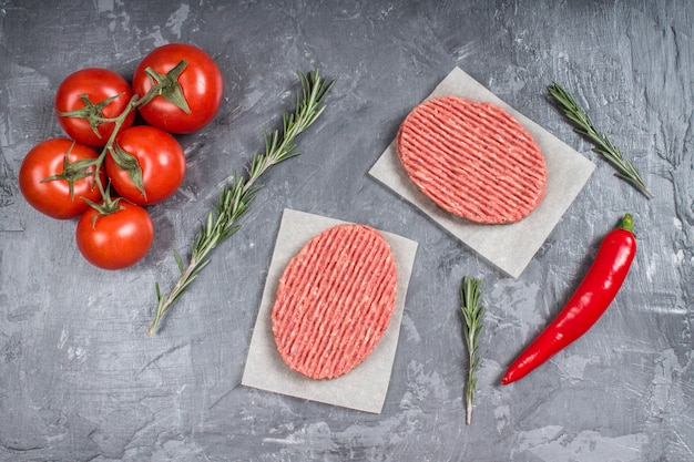 Hamburger crudi su carta pergamena con pomodori, peperoncino e rosmarino. Foto Premium