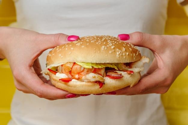 Hamburger dei frutti di mare con i gamberetti che tengono in mani della giovane donna Foto Premium
