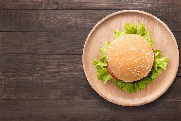 Hamburger del bbq di vista superiore sul piatto di legno su fondo di legno. copia spazio per il testo Foto Premium