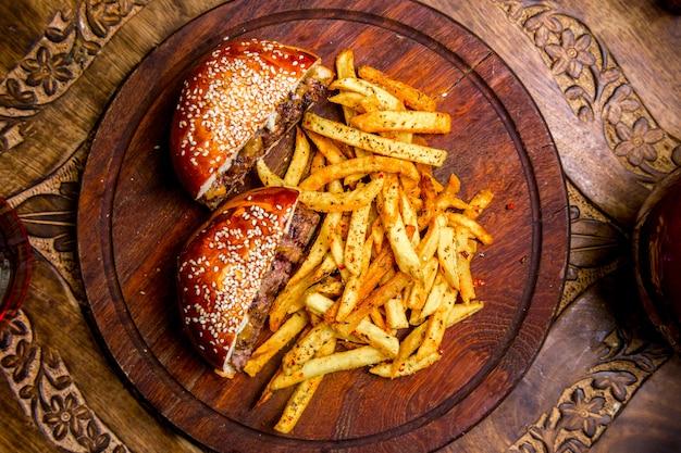 Hamburger della carne sulla vista superiore delle patate fritte del bordo di legno Foto Gratuite