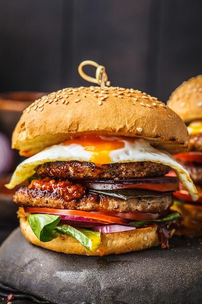 Hamburger di carne fatta in casa con uova, salsa e verdure su sfondo scuro. Foto Premium